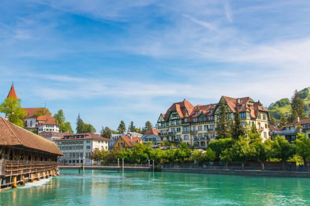 das stadtzentrum von thun, schweiz mit alten gedeckte holzbrücke über den fluss aare. - thun switzerland stock-fotos und bilder