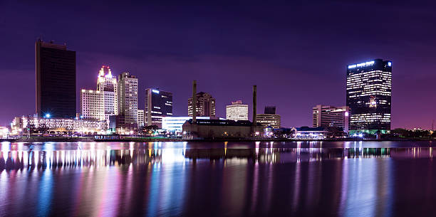 The city lights of a skyline reflecting on the water stock photo