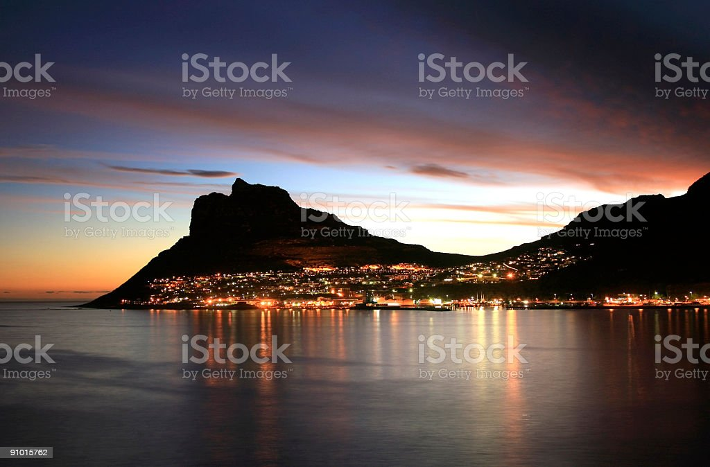 The city lit up at sunset in Hout Bay stock photo