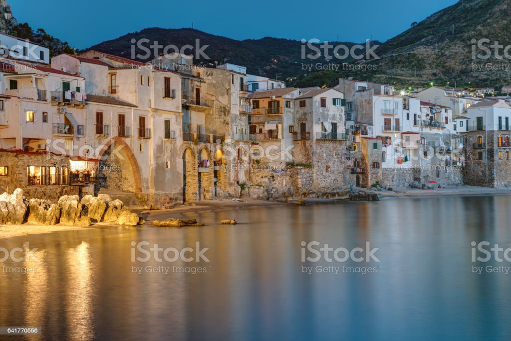 The city of Cefalu reaches right to the beach stock photo