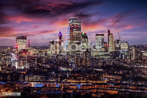 The City of London, financial district of the Metropole, just after sunset with illuminated buildings and cloudy sky, United Kingdom