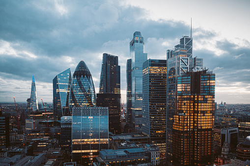 Aerial panoramic view of The City of London cityscape skyline with metropole financial district modern skyscrapers after sunset on night with illuminated buildings and cloudy sky in London, UK