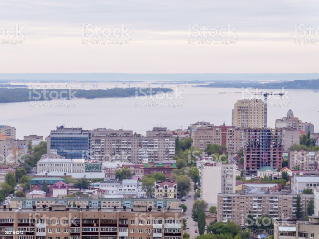 城市的天際線。俄羅斯的薩拉托夫省。高層住宅樓、 伏爾加河和鐵路橋梁在地平線上 免版稅 stock photo