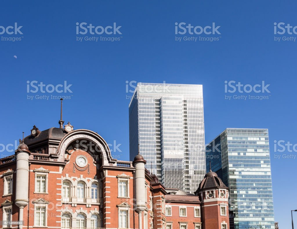 The classic architecture of the Tokyo JR train station contrasts with modern office building in the buisiness district of Marunouchi in Tokyo stock photo