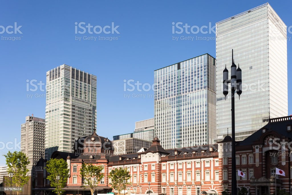 The classic architecture of the Tokyo train station contrasts with modern office building in the buisiness district of Marunouchi in Tokyo stock photo