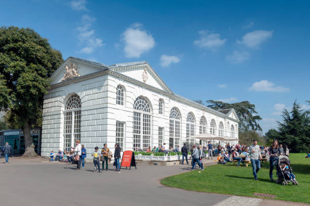 The classic white building of The Orangery restaurant and cafe setting among lush botanic area at Kew Gardens in Richmond upon Thames, England stock photo