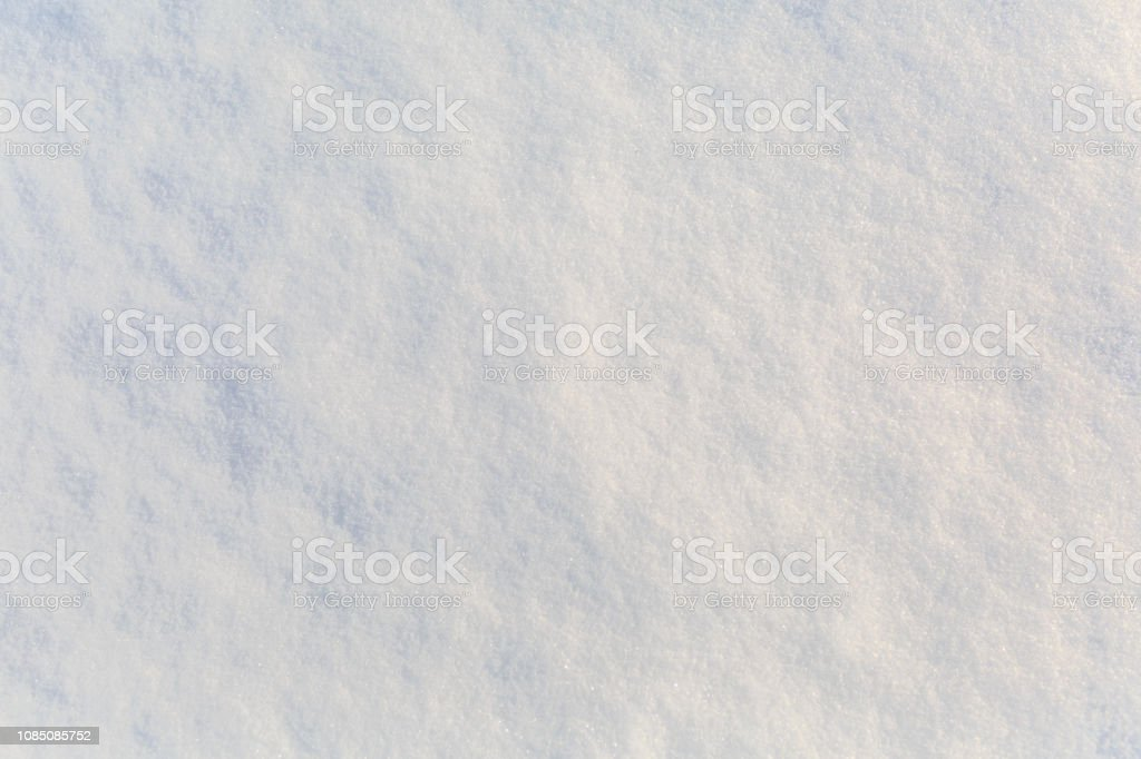The clean surface of white fluffy snow in the sunlight as a background or backdrop stock photo