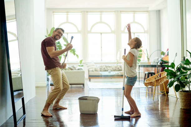 The cleaning rockstars Shot of a handsome mature man and his daughter mopping the floors in their home as part of their spring cleaning cleaning equipment stock pictures, royalty-free photos & images