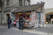 Bern, Switzerland - April 17, 2017: Clients stand in front of the kiosk and watch things like small souvenirs also drinks, daily newspapers and other items needed by tourists arriving here. This is one of the countless wonderful places in Switzerland, which is a tourist attraction often visited by many tourists from all over the world.