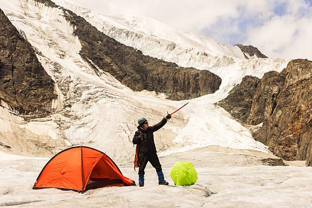 die kletterer kosten auf gletscher in der nähe von zelt - zelt stehhöhe stock-fotos und bilder