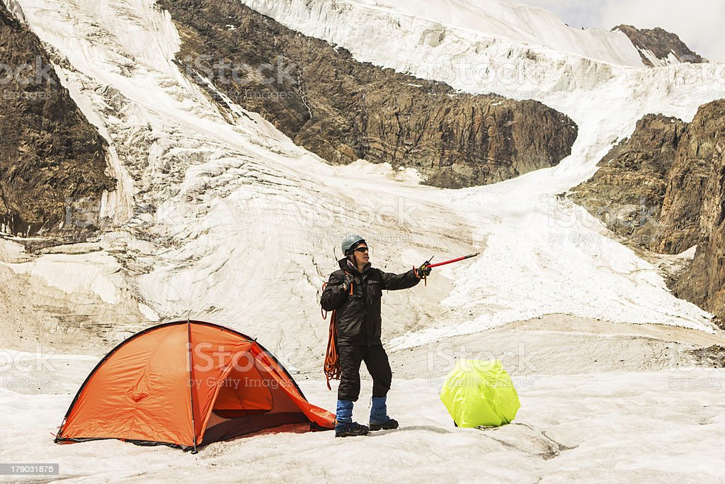The climber standing near tent on glacier royalty-free stock photo