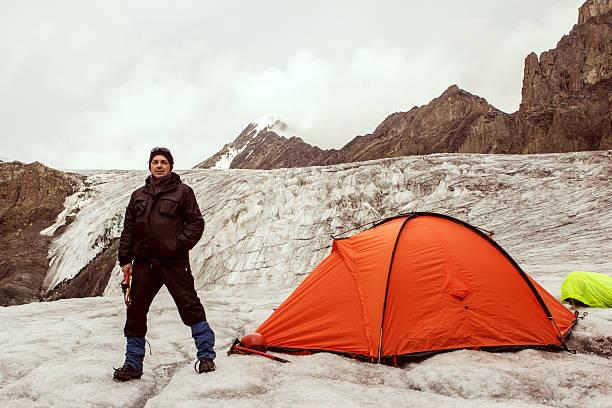 der stepper stehen in der nähe von zelt auf gletscher - zelt stehhöhe stock-fotos und bilder