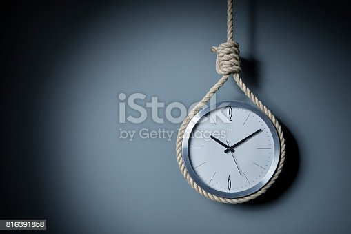 The clock hangs itself with a Hangman's noose in front of a grey wall.