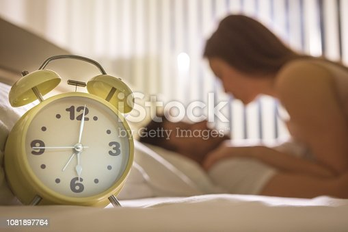 istock The clock on the background of the couple in the bed 1081897764