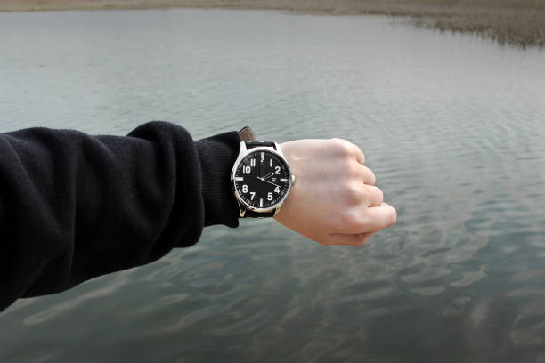 The clock on the hand on the background of water stock photo