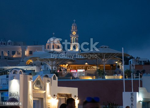 Fira, Greece - July 14 2019:   The clock tower and dome of St John the Baptist cathedral at night seen from Ipapantis