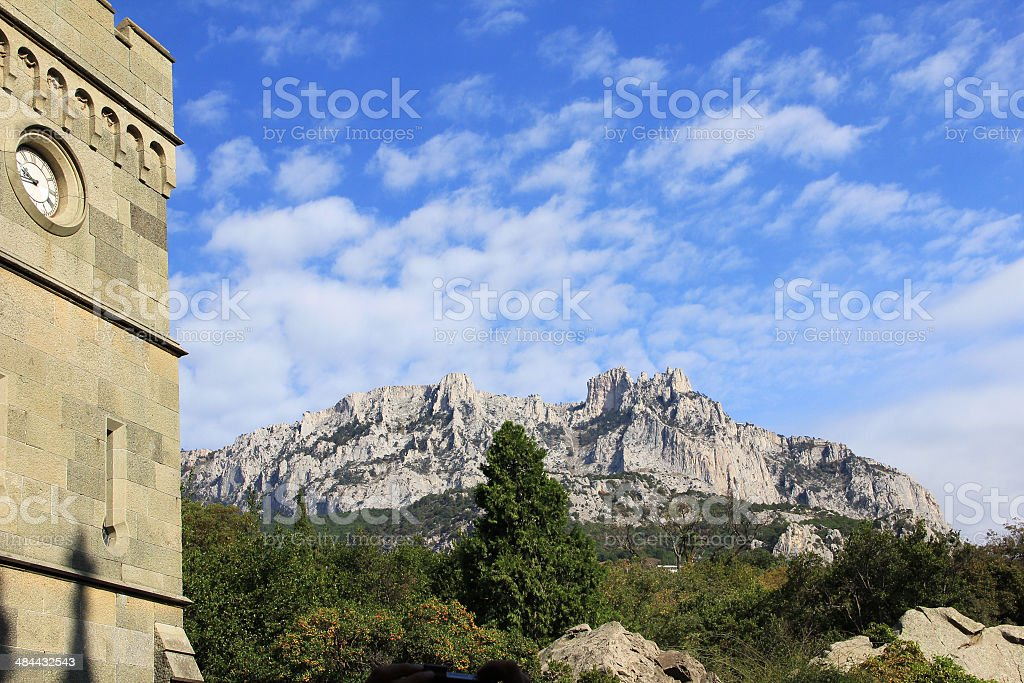 The clock tower on the background of the Crimean mountains stock photo