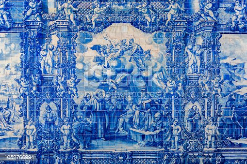 937530990 istock photo Porto, Portugal - November 17, 2017: The cloister walls of Porto's Cathedral are decorated with the traditional Portugese blue and white painted tin-glazed ceramic tiles called Azulejos. 1052766994