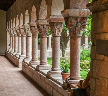 A visitor enjoys a courtyard in the Cloisters Museum, NYC.