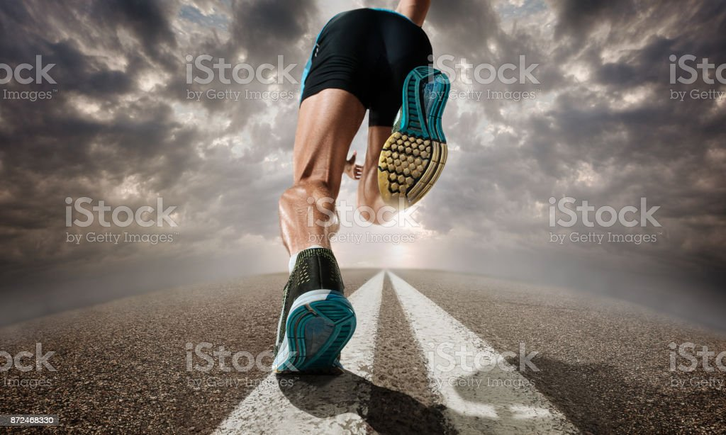 The close up feet of man running and training on running track stock photo