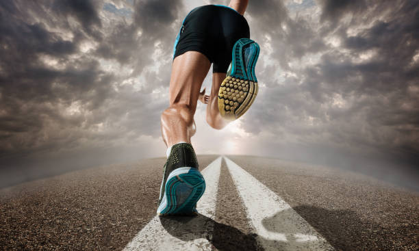 the close up feet of man running and training on running track - marathon stock photos and pictures