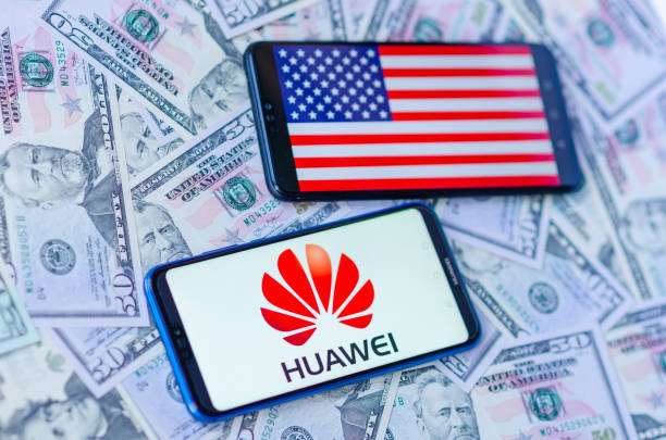 The close up photo of two mobile phones on dollar bills with Chinese HUAWEI logo and American flag. The conceptual editorial photo shows US China trade war. Conceptual image for the news about US blacklisting the Chinese tech giant Huawei. Huawei suffers billion dollars loss in profits. huawei stock pictures, royalty-free photos & images