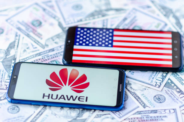 the close up photo of two mobile phones on dollar bills with chinese huawei logo and american flag. the conceptual editorial photo shows us china trade war. - huawei foto e immagini stock