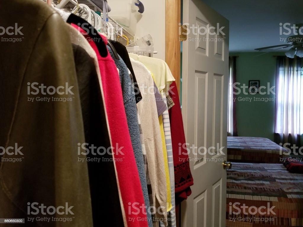 El espacio cerrado. Ropa en los colgadores, en el estante y el organizador del armario en el armario. - foto de stock