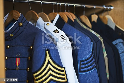 Shot of various military jackets hanging in a closet
