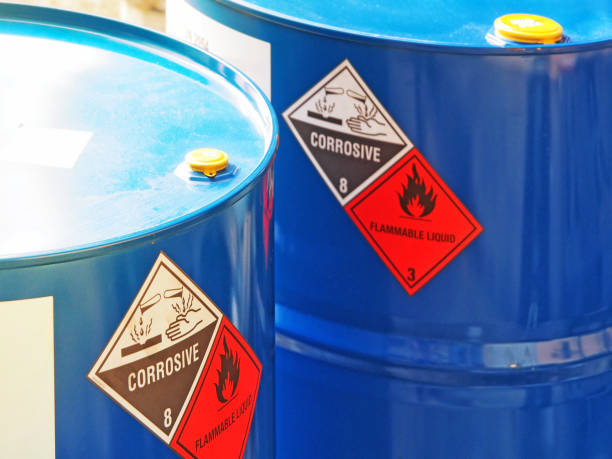 the close-up shot of blue color hazardous dangerous chemical barrels. the close-up shot of blue color hazardous dangerous chemical barrels ,have warning labels of corrosive & flammable liquid in daylight on daytime. hazardous chemicals stock pictures, royalty-free photos & images