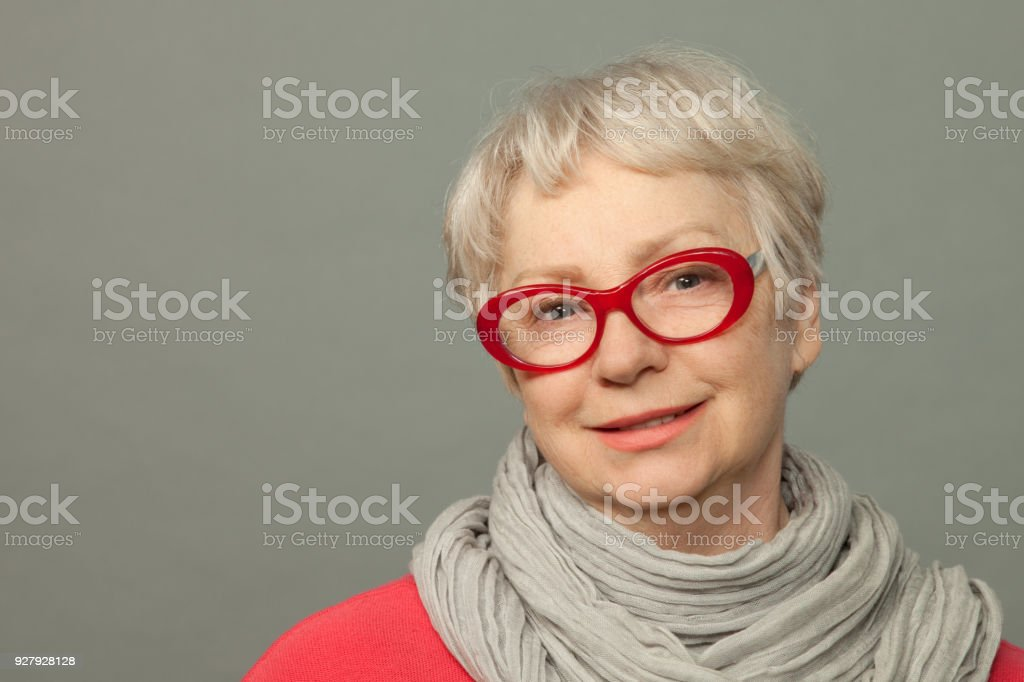 The closeup studio portrait of the attractive senior 65-years-old woman stock photo