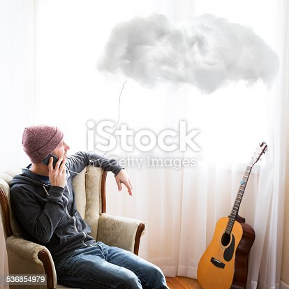 A young man in his home talks on his smart phone while the cloud floats nearby.  The phone is plugged into the cloud.