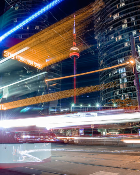 The CN Tower at night, seen between two waterfront buildings with light trails from a 509 Harbourfront street car.