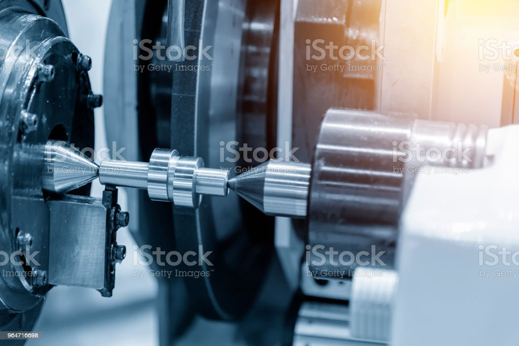 The CNC cylindrical grinding machine grinding  the motorcycle cam shaft in the light blue scene. royalty-free stock photo