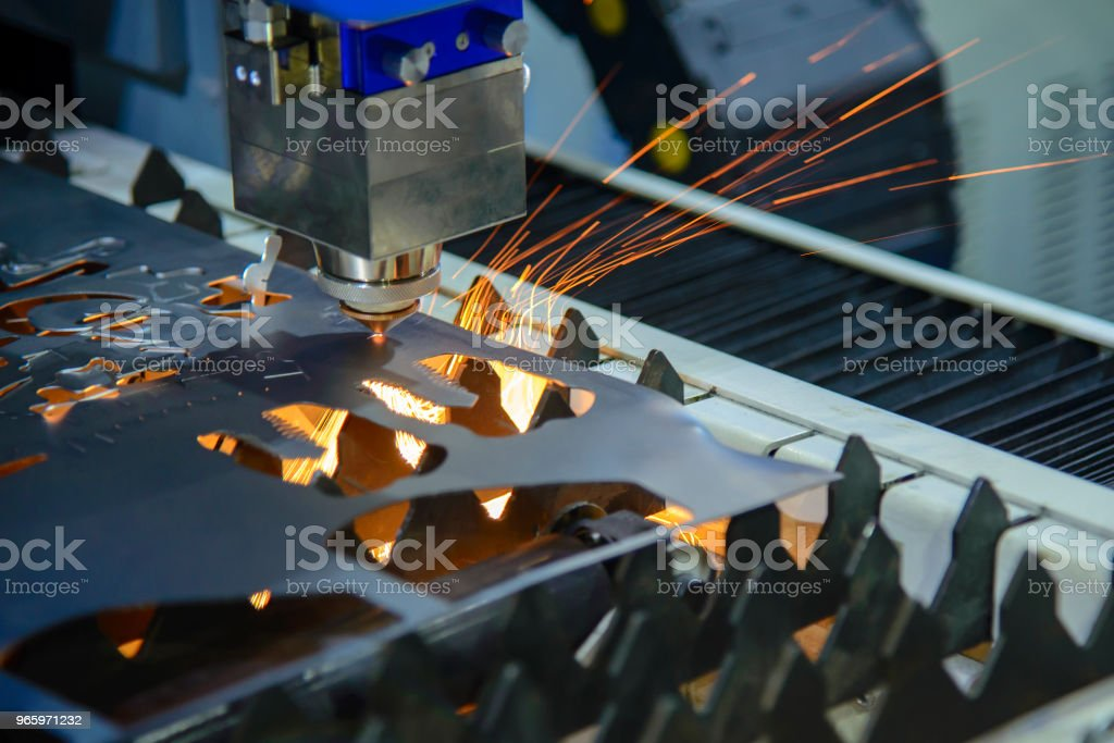 The CNC laser cutting machine cutting the metal plate with the sparking light. - Royalty-free Accuracy Stock Photo