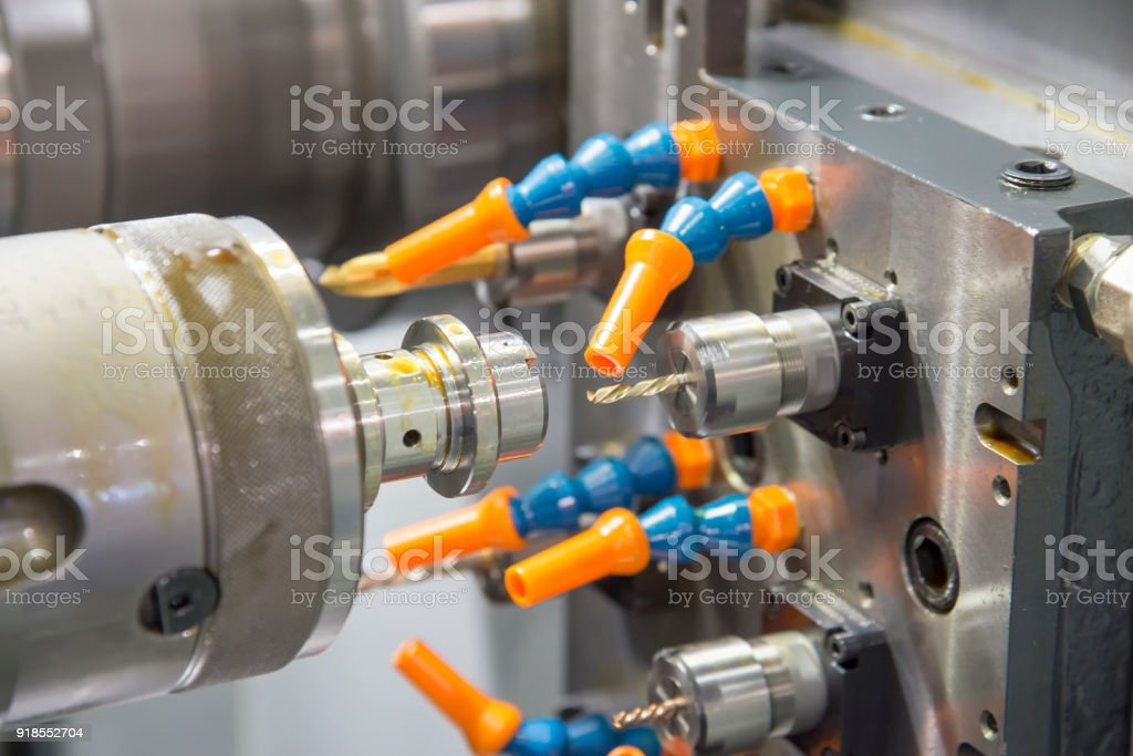 The  CNC lathe machine cutting the  metal shaft with the drill tool. stock photo