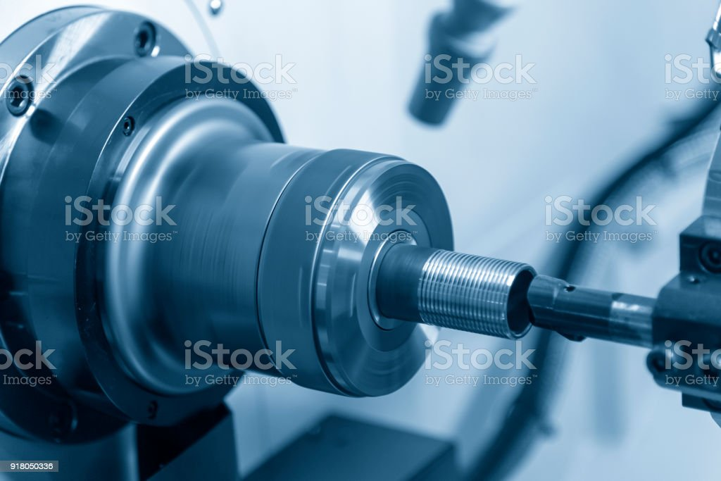 The CNC lathe machine cutting the thread at the end of the pipe. stock photo