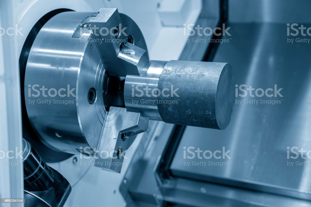The CNC lathe or turing machine cutting the raw material in the light blue scene. zbiór zdjęć royalty-free