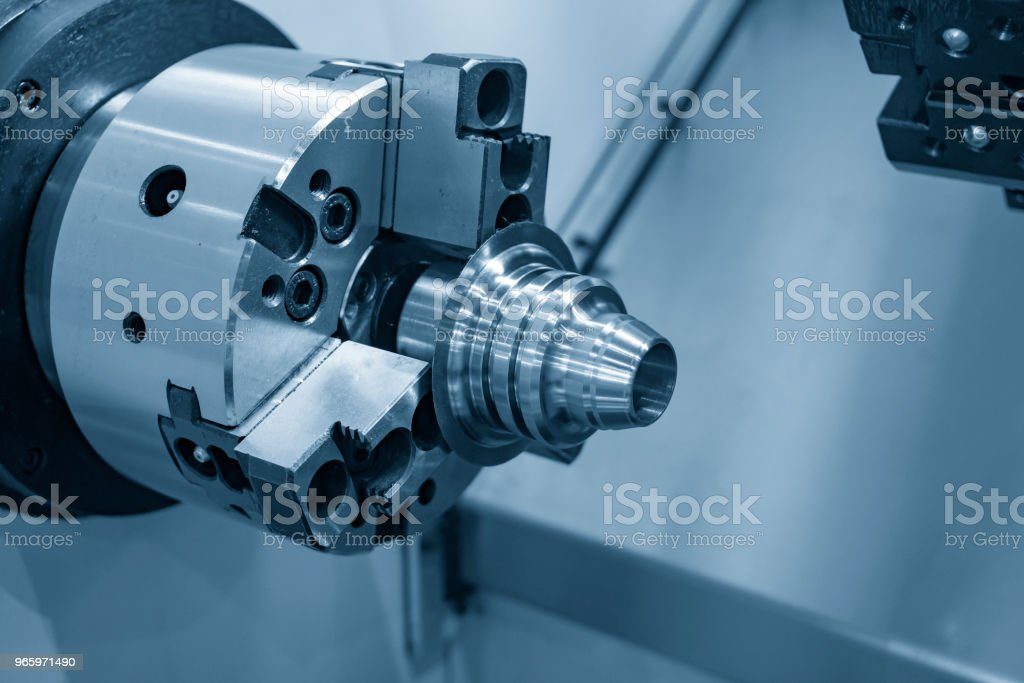 The CNC lathe or turning machine cutting the metal cone shape part in the light blue scene. - Royalty-free Accuracy Stock Photo