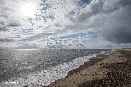 The coast of East Anglia Norfolk UK. Coastal view with cloudy sky, pebbled beach and distant offshore wind farm turbines. Changeable weather from the sea.