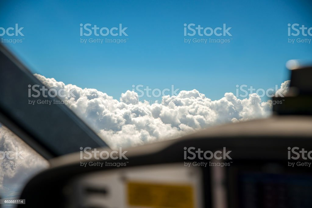 The cockpit of a small aircraft flying at seven thousand feet with the selective focus on the altocumulus clouds outside the front window. stock photo