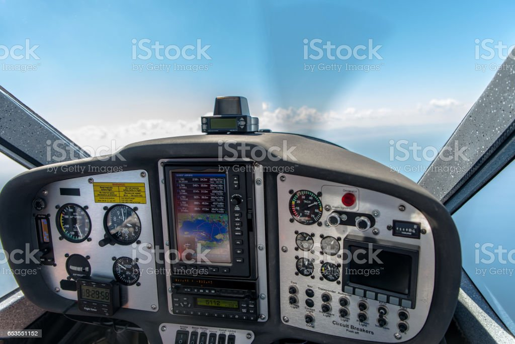 The cockpit of a small aircraft flying at seven thousand feet with the selective focus on part of the control panel. stock photo