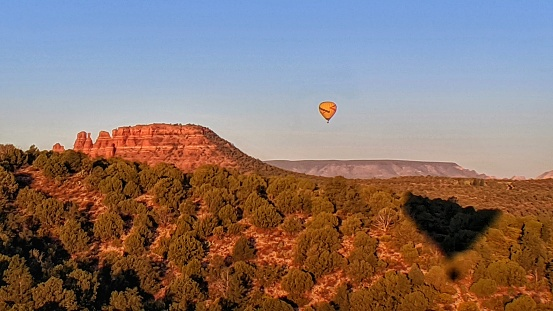 Sunrise over the Red Rock Country with hot air balloon's shadow in the foreground and another balloon near the Cockscomb Butte in the background. Sedona, AZ. October 20, 2019.
