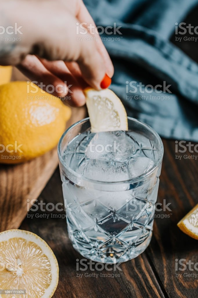 The cocktail with club soda, vodka, lemon and ice on a wooden table. Retro or vintage toned image. stock photo