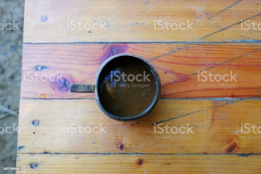 The coffee in the glass from natural coconut shell on wooden table stock photo