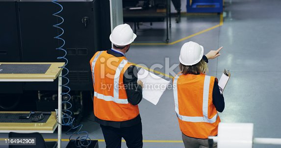 Shot of two engineers discussing paperwork in an industrial place of work