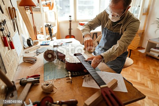 Man painting homemade guitar to make the sound better