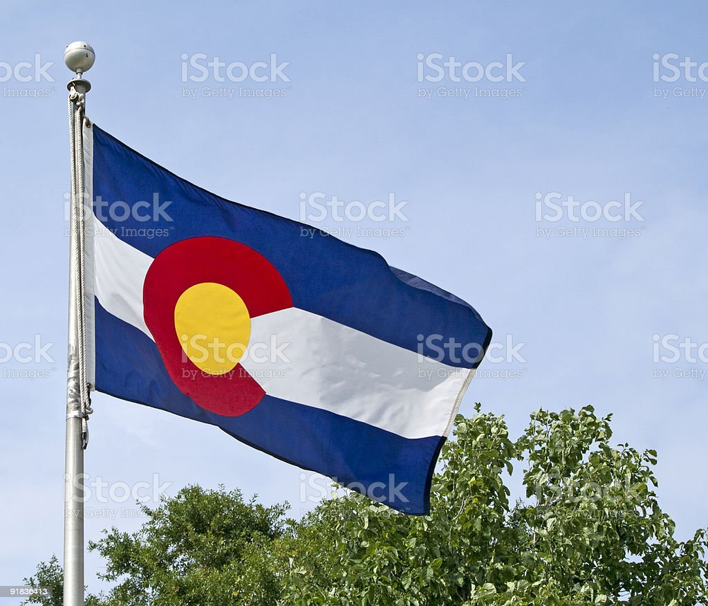 The Colorado State flag in front of a tree and a blue sky stock photo