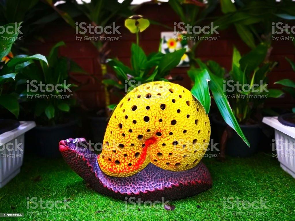 Photo libre de droit de Lescargot En Céramique Colorée Avec Coquille Jaune  Et Violet Corps Qui Est Sur Le Gazon Artificiel Vert Et Décoré Dans Un  Petit Parc Public Sélective Focus Et