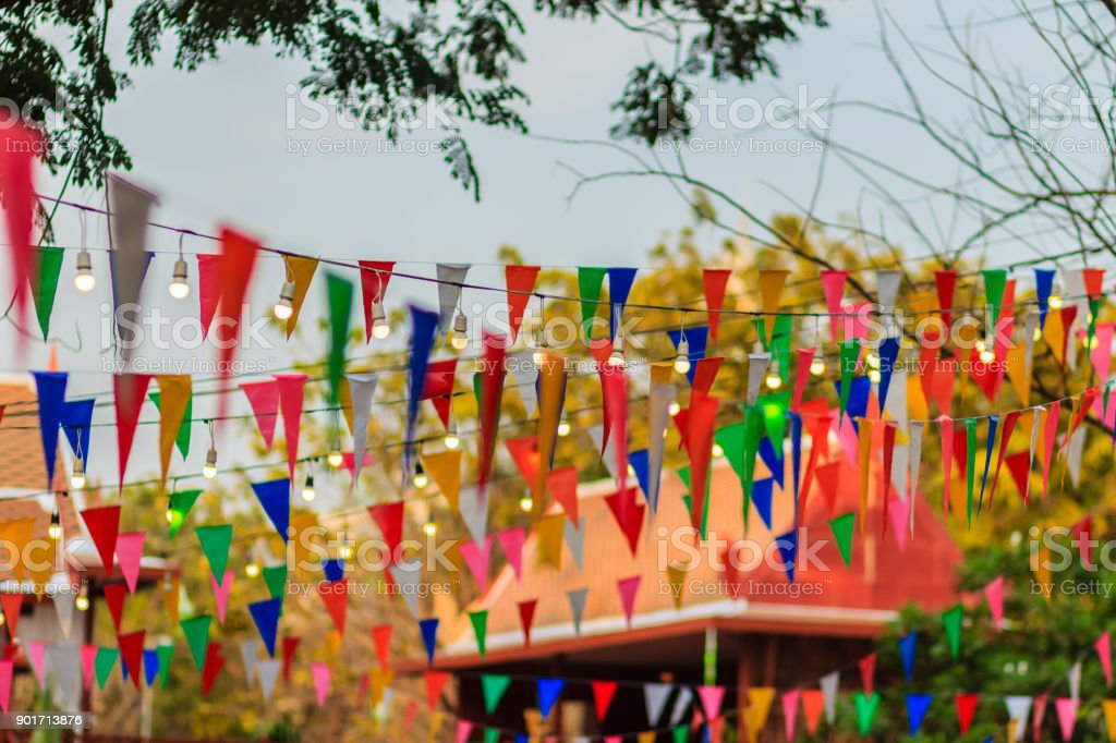 The colorful flags between the trees in Thai style temple festival. stock photo